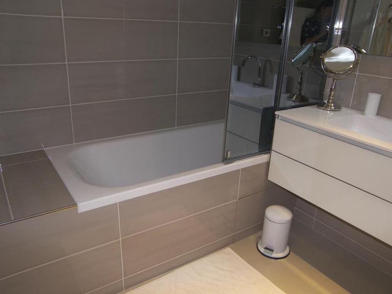 White bathtub with mud coloured tiles