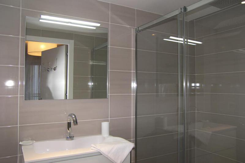 Washroom with beige tiles and standing shower