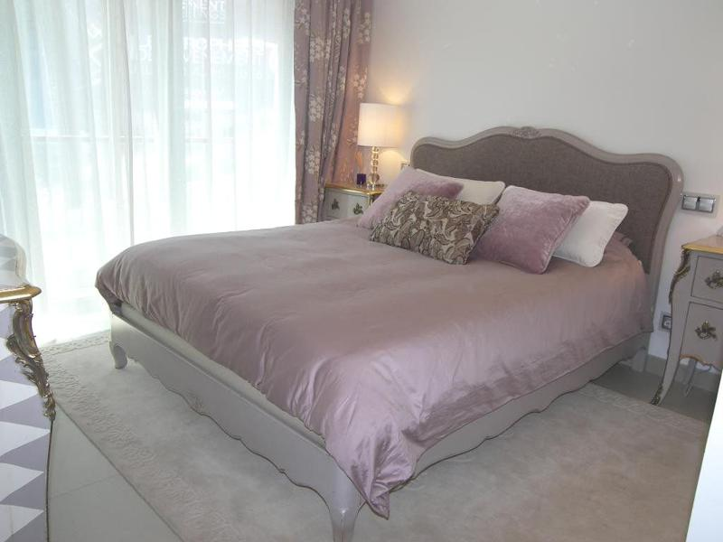 Double bedroom with pink blanket and beige coloured rug in a Cannes accommodation