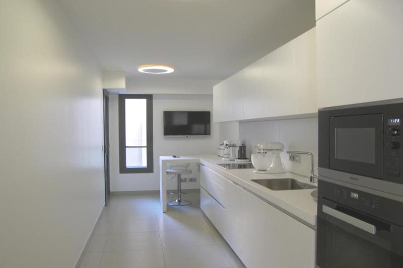 Kitchen with white interiors and a wall mounted tv in Cannes