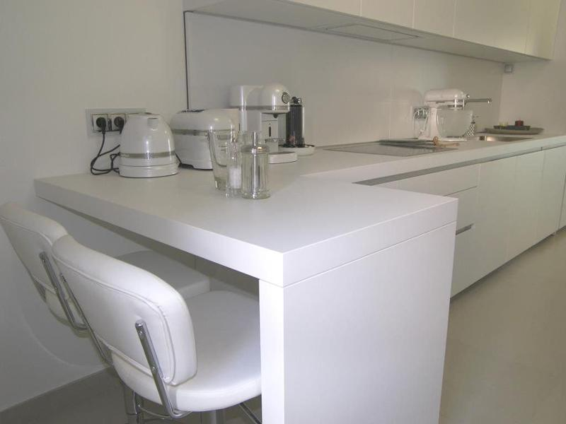 White bar stools, countertops and walls in a kitchen with a coffee maker, an electric water boiler and a toaster