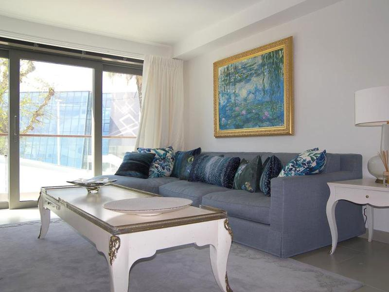 White tables and curtains in a living room with a couch set and a painting on the wall in Cannes