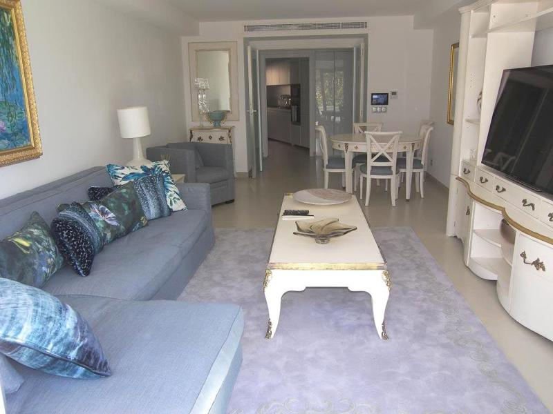 Living room with a couch, a flat screen tv and a white table with chairs for group accommodation facing Palais des Festivals