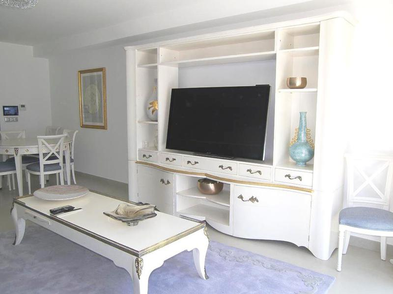 Flat screen tv inside a white cabinet with artefacts on the shelves