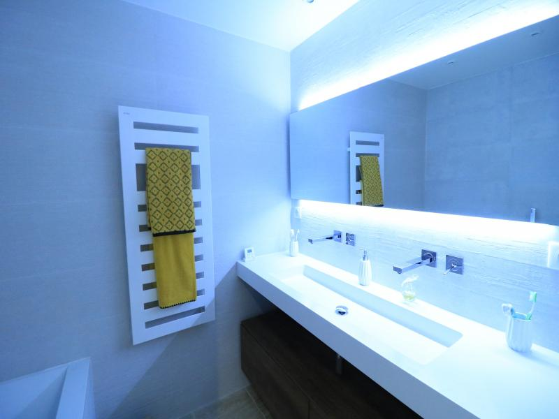 White long sink with a mirror and blue neon lights in a bathroom