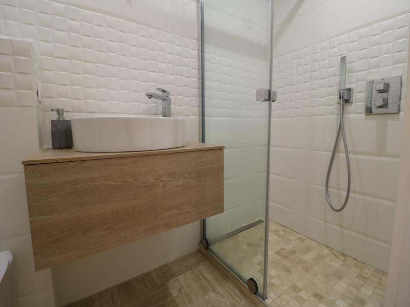Glass enclosed standing shower in a bathroom with wooden framed sink
