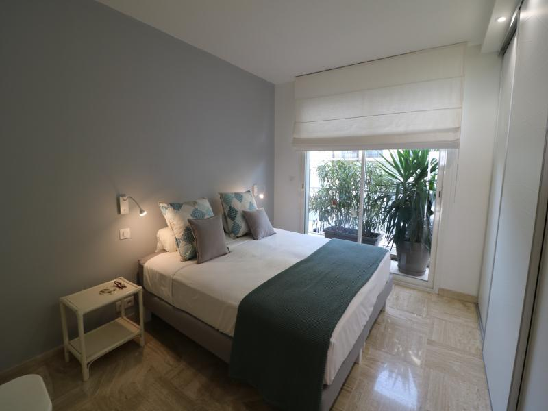 Double bed in a bedroom with grey and white interiors and attached private balcony in Cannes