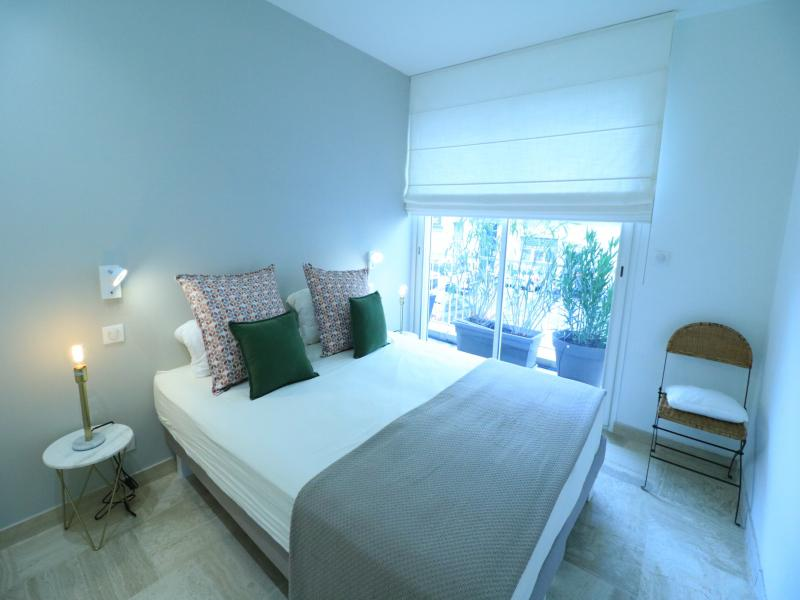 Double bed with white sheets, grey cover and a chair in the corner in the bedroom with terrace in Cannes