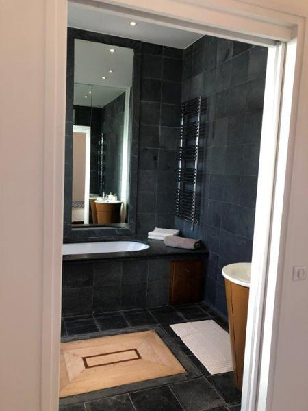 Black tiles and white bathtub in the bathroom in Cannes