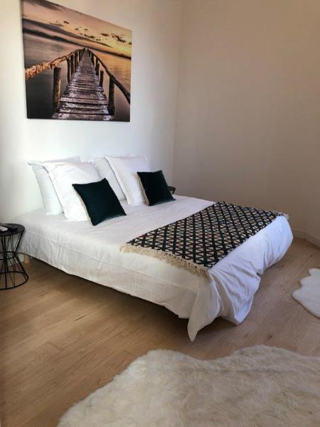 Double bed with wooden floor and white covers in a Cannes event accommodation