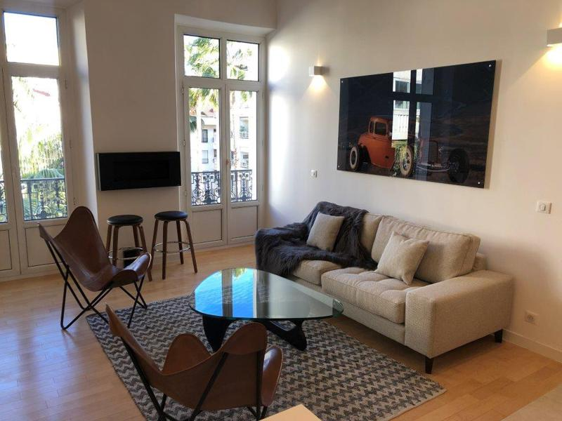 Living room with a couch, chairs and bar stools in a Cannes 2 bedroom rental apartment for events