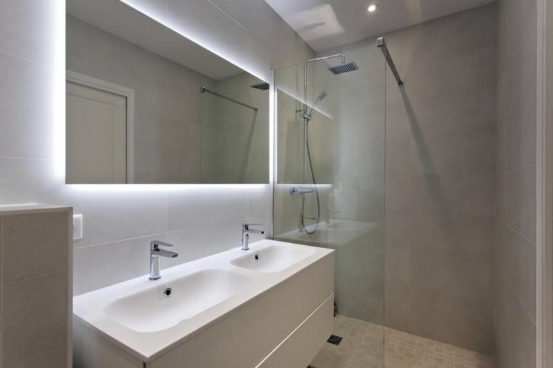Standing shower in the bathroom with a dual sink and a large rectangular mirror