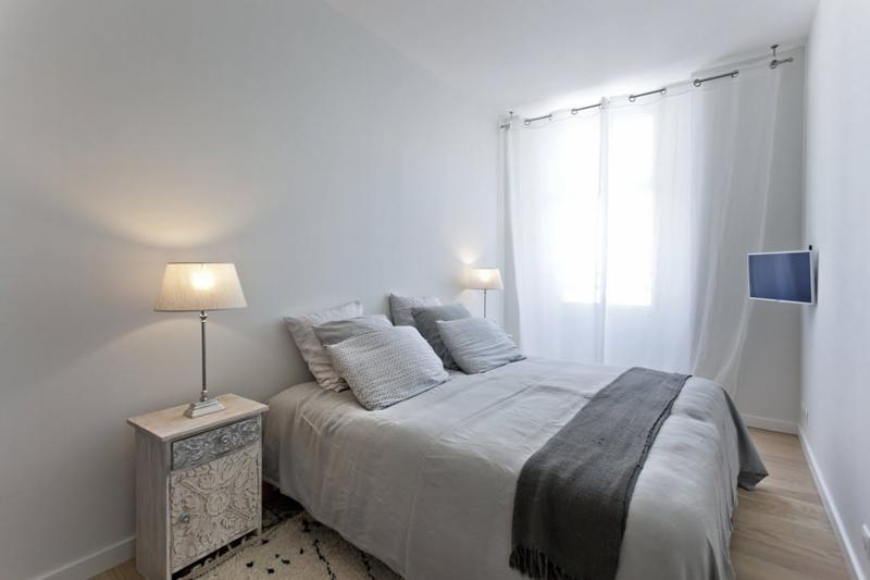 Double bedroom with grey blanket and pillows in the bed, a side table with a lamp and a tv in the corner