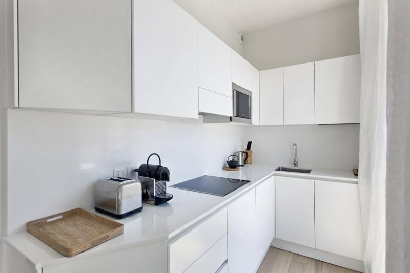 Coffee maker, toaster, microwave, water boiler and induction stove in a Cannes kitchen with shiny white cabinets