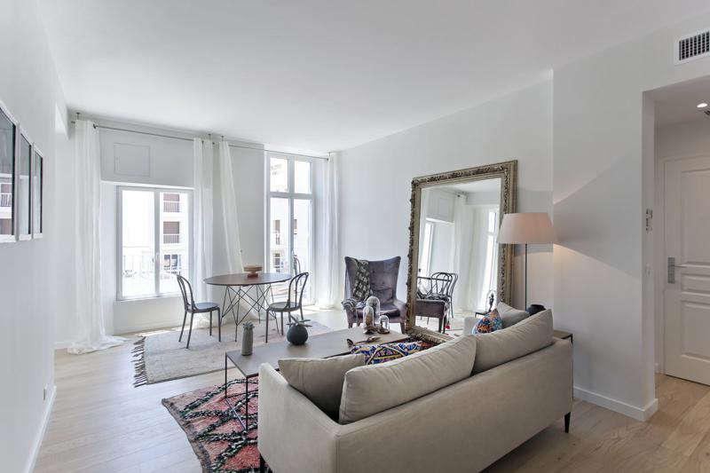 2 bedroom Cannes rental apartment's living room with an overall beige tone and a large glass door with access to the terrace