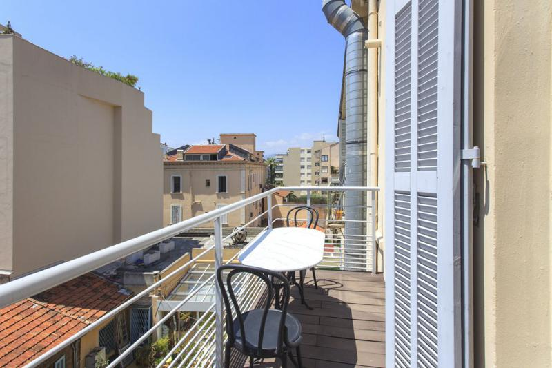 Sunny terrace with a table and 2 chairs in a Cannes corporate accommodation with street view of Rue d'Antibes