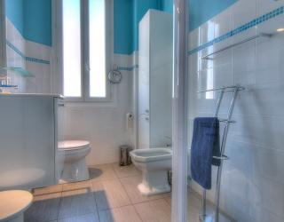 Bathroom with white and blue tiles, a shower and a toilet.
