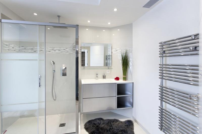 Modern bathroom with white interiors and a glass enclosed standing shower in Cannes