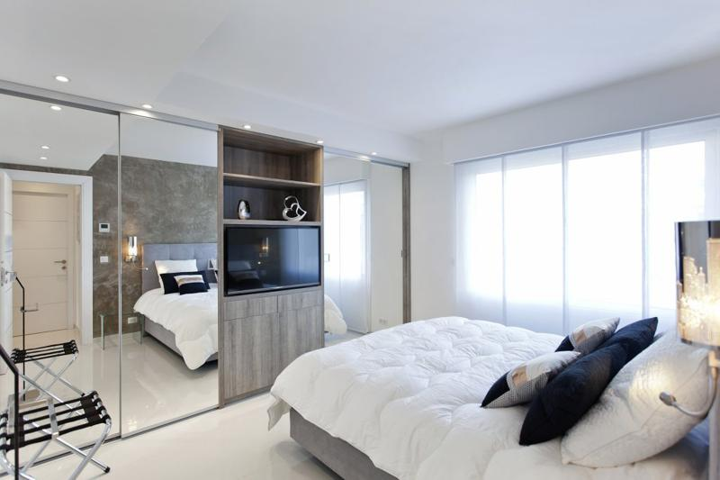 White curtains on the windows in a modern double bedroom with a tv facing the bed and a glass wall closet.