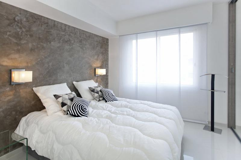 Double bedroom with white pillows, blanket and curtains in a marble floored bedroom in Cannes