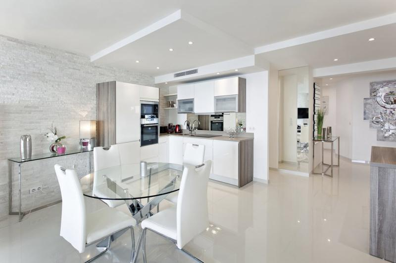 Marble flooring in a Cannes rental apartment with an open kitchen and a glass table with chairs for meeting