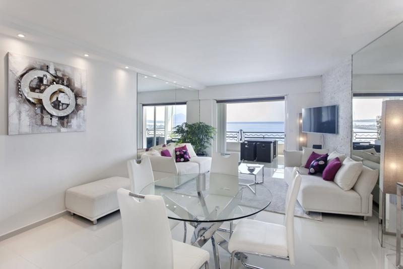 Circular glass dining table with white leather chairs in the living room of a Cannes group apartment by the sea for rent