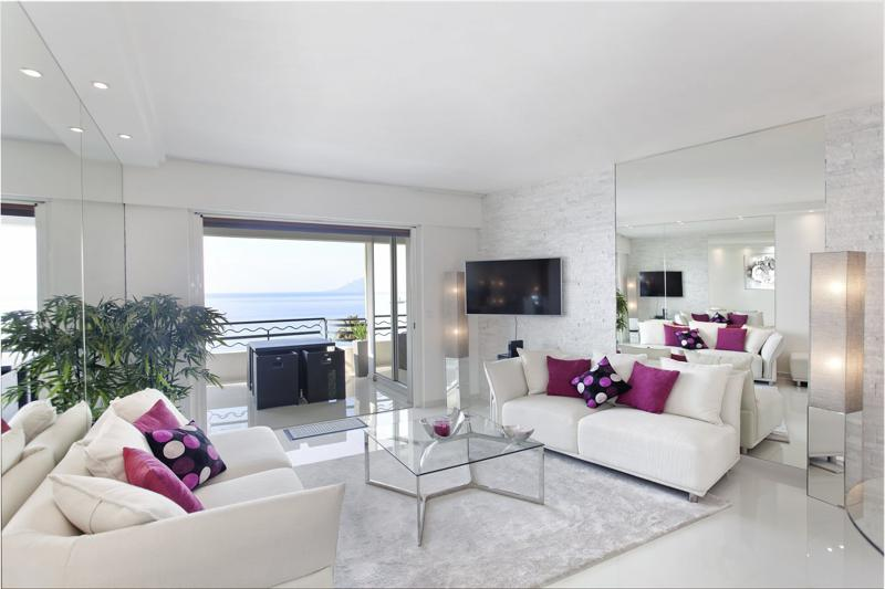 Couch sets with pink cushions in the living room of a 2 bedroom modern Cannes corporate rental apartment by the sea