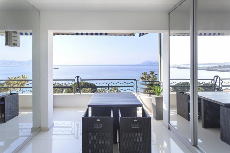 Sea facing terrace with patio furniture in a Cannes event apartment on the Croisette
