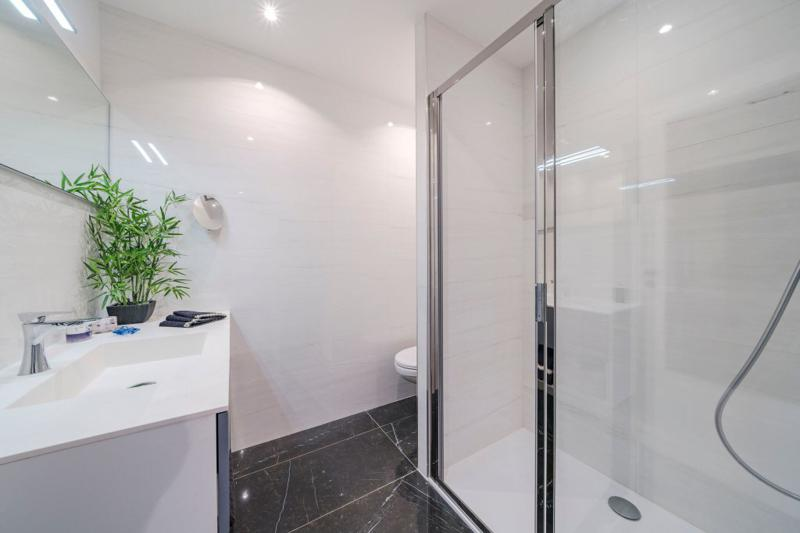 White interiors in the bathroom with standing shower and a toilet in Cannes