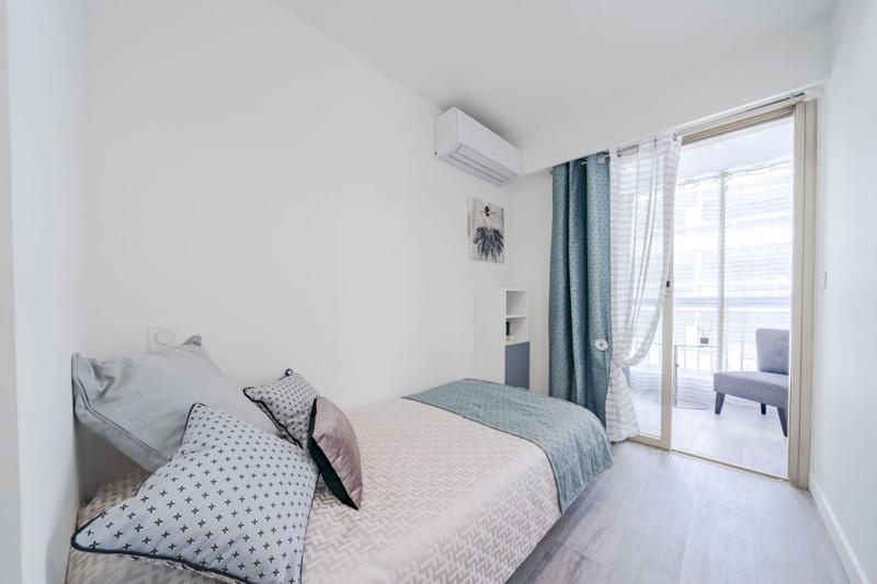 Single bedroom with white wall paint, air conditioner and separate meeting space in Cannes