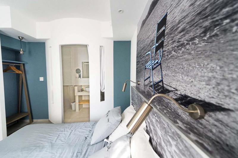 White and blue painted walls in a double bedroom with a clothing rack and attached bathroom in Cannes