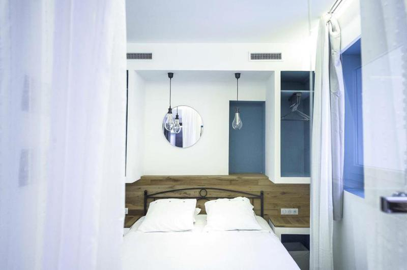 Double bedroom with white sheets and pillows, an open closet with hangers and hanging bulbs in a Cannes rental apartment
