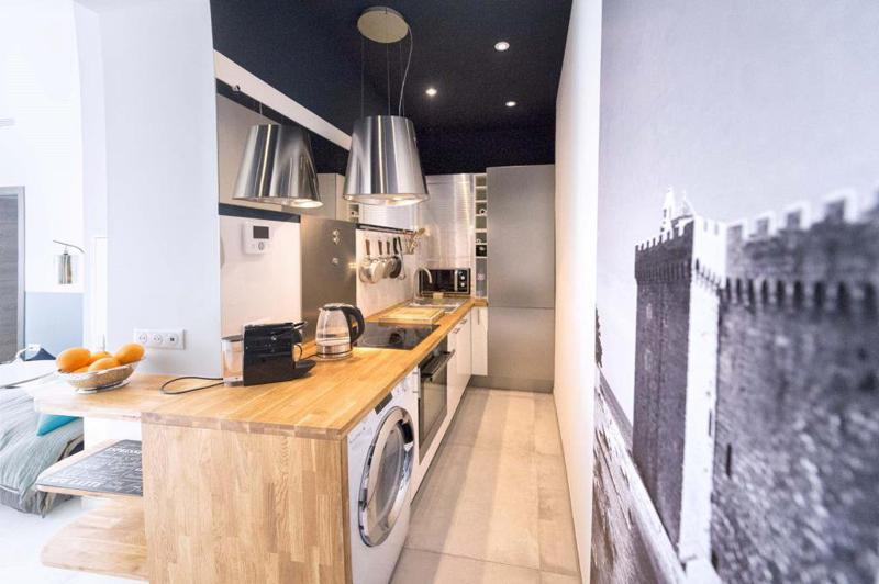 Kitchen with wooden countertops, a washing machine, coffee maker, water boiler and microwave in a Cannes central apartment