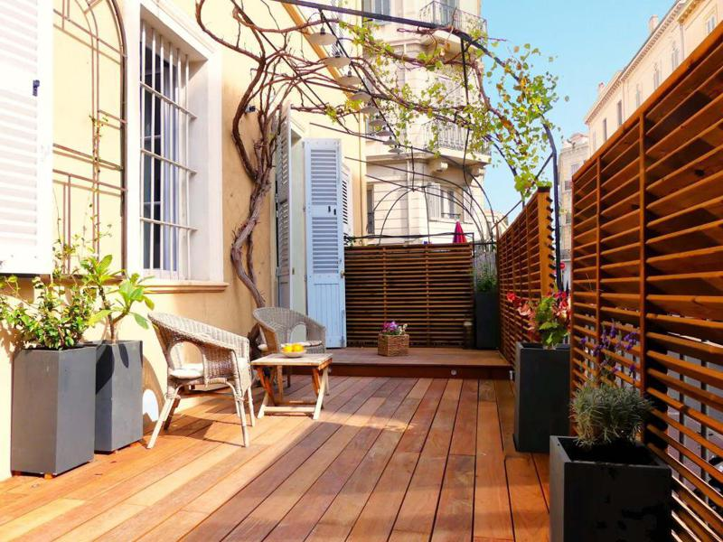 Teak terrace with patio furniture and hanging garden in a Cannes group rental apartment near to the Palais des Festivals