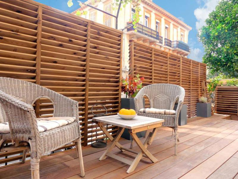 Outdoor terrace furniture with chairs and a table in a Cannes ground floor party apartment for groups in the city centre