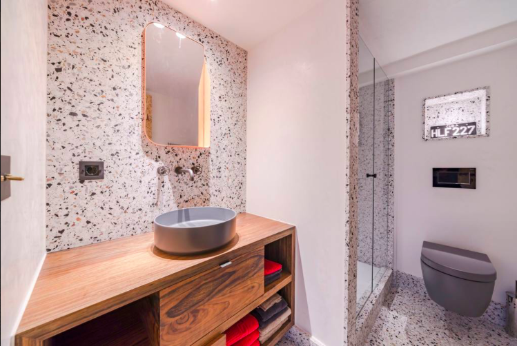 Modern bathroom with glass enclosed standing shower, a toilet and a sink with a wooden frame in Cannes