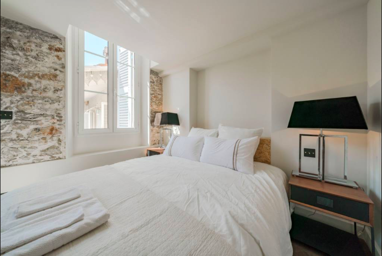 Double bedroom with white sheets and pillows, a windows with Cannes views and side tables with lamps