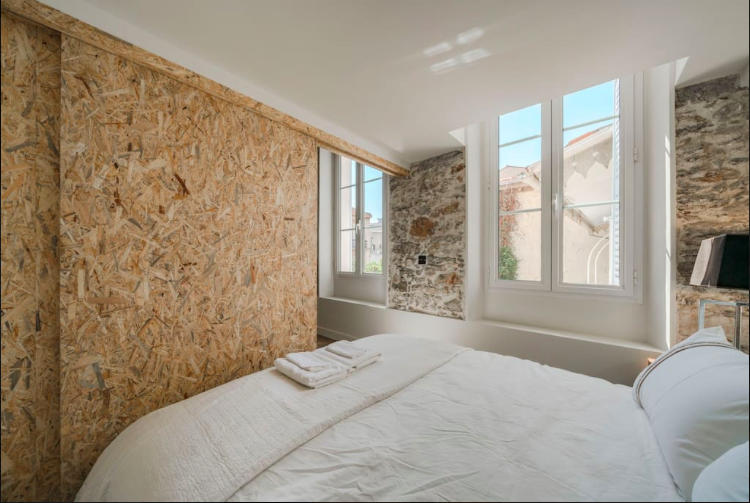 Stonewall bedroom with a double bed and windows with outside views in Cannes