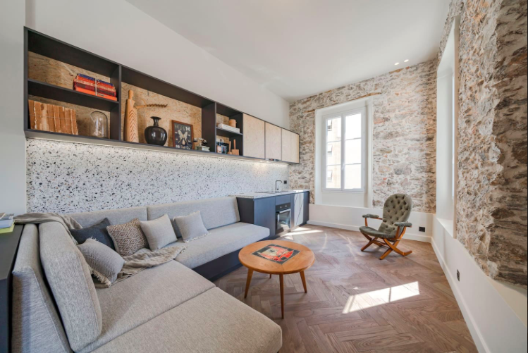 Living room of a modern Cannes 1 bedroom apartment for rent with stone walls, couch set and an open kitchen
