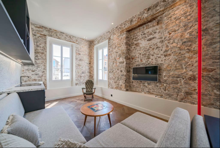 Tv mounted on stone walls, facing couch sets in the living room with windows and an open kitchen in Cannes