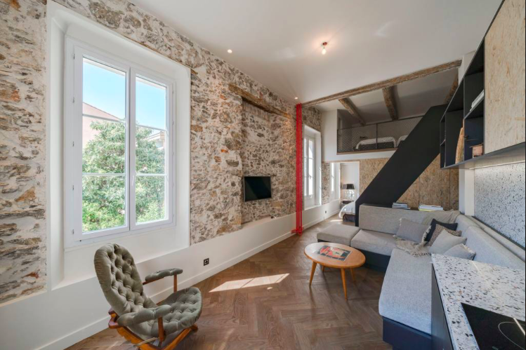 Artistic stone walls in the living room with natural light and outdoor view in a Cannes rental apartment in Rue Marceau