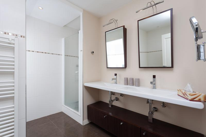 Bathroom with a standing shower , a dual sink and 2 mirrors
