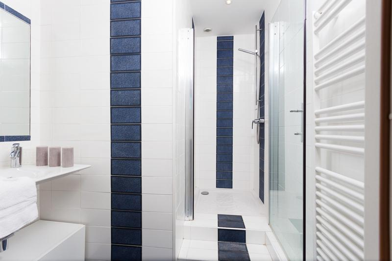 Blue and white tiles in the bathroom with a standing shower, a sink and a mirror