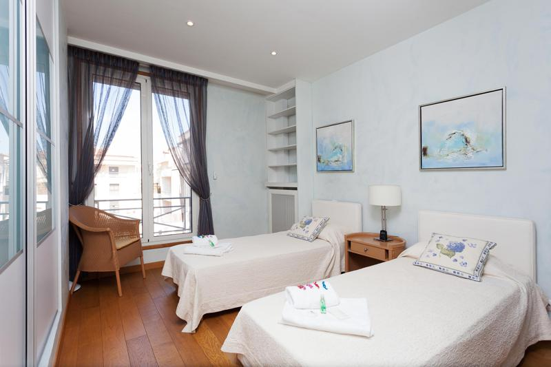 A table in the middle of 2 single beds with cream blankets and a chair in the corner of the bedroom with a balcony in Cannes