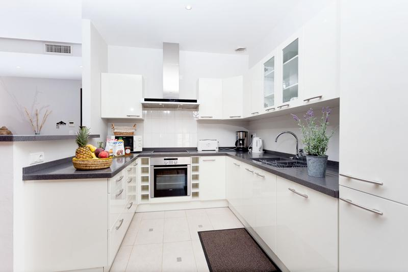 Kitchen with white cabinets, oven, fresh fruits, coffeemaker and a toaster in Cannes