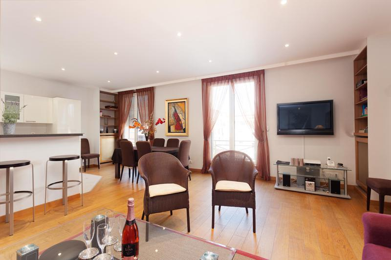 Champagne bottle with glasses on the table, bar stools in the kitchen and an open dining area in a Cannes event accommodation