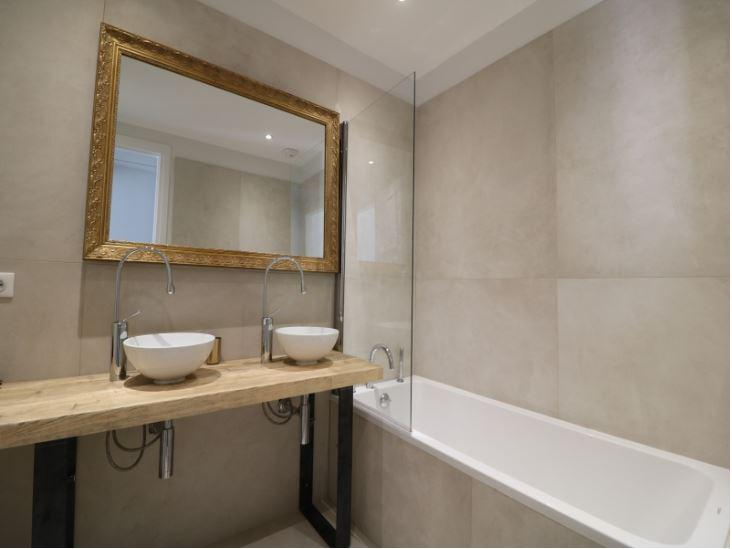 Beige coloured wall tiles in a modern bathroom with bathtub and dual sink in Cannes