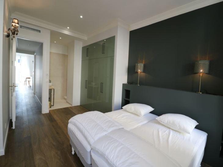 2 singles beds joined together in a Cannes bedroom with spacious wardrobe, white sheets and pillows and an attached bathroom