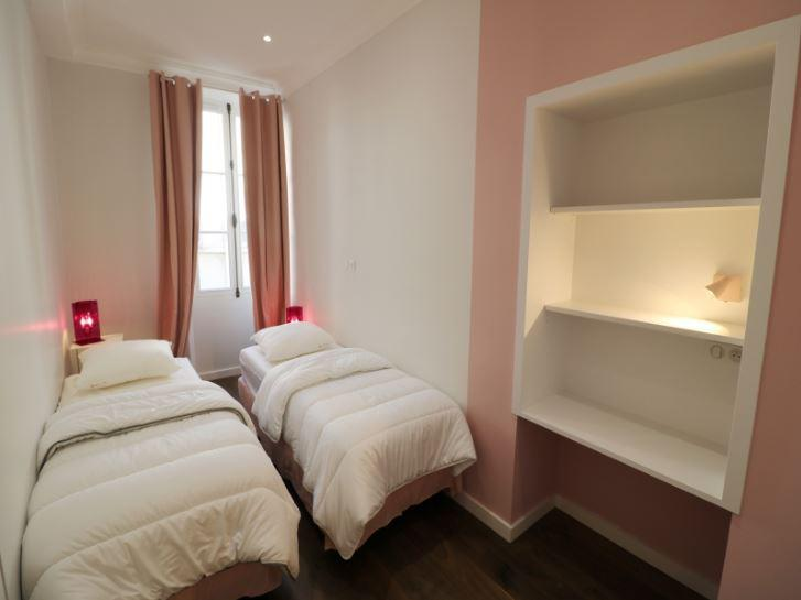 2 single beds with white pillows and blankets in a bedroom with pink curtains and natural light in Cannes