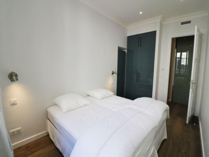 2 single beds with white sheets, pillows and blankets joined together in a room with wooden floor